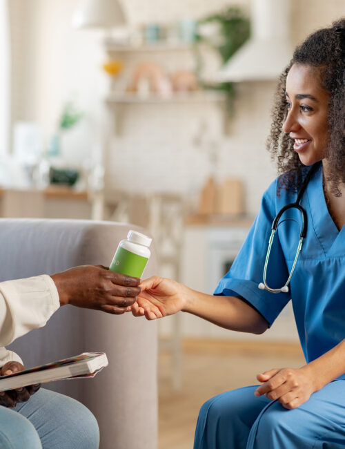Thankful aged woman taking pills from caring medical attendant